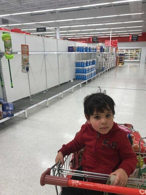 a child sitting in a supermarket trolley in an empty supermarket