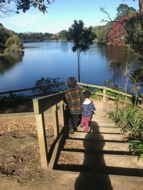 image of two children standing in front of a lake