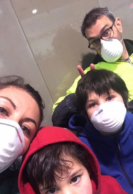 two adults and two children with face masks on